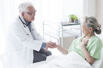 A geriatric doctor gently holding a hand of a female patient with a smile