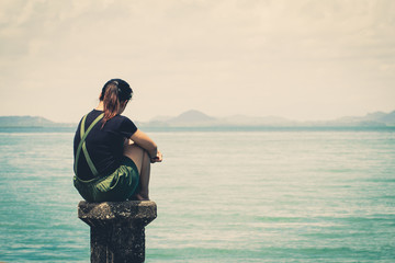 The girl sitting alone lonely at the sea. With loneliness