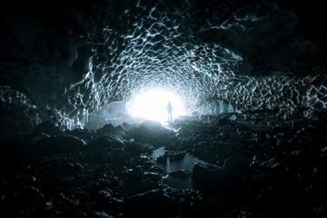 Mysterious Ice cave in Germany with young adult male standing in the light