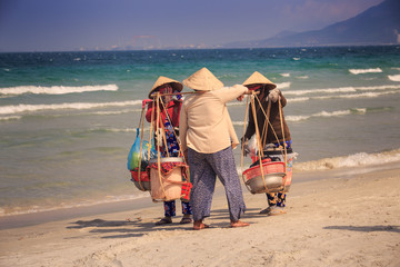 Local Sellers with Goods in Baskets Meet on Ocean Beach