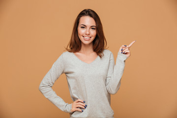 Beautiful smiling young woman in casual wear pointing with finger, looking at camera