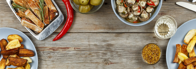 Dining table with a variety of meals and snacks. Meatballs, baked potato wedges, meat, mushrooms, ketchup. Rustic style. Wooden background, top view.