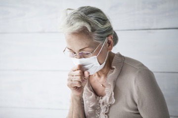 Portrait of an old woman holding a cold