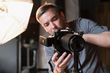 the young man adjusts the camera during photographing in the Studio