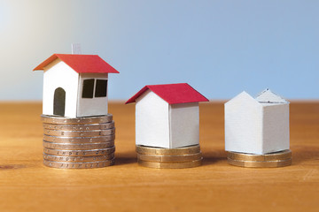 Three paper house on coin's piles, mortgage, loans and saving concept