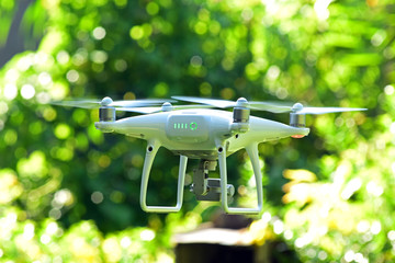 Drone hovering on green nature bokeh background