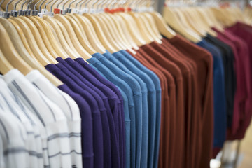 selective focus hand holding color Dress cloth and Shirts hanging stack,in the row
