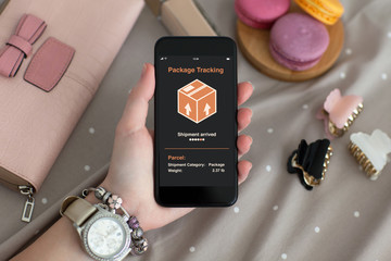 female hand holding phone with app tracking delivery package
