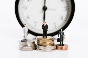 Miniature business people stand on silver coins with alarm clock background,time is money concept