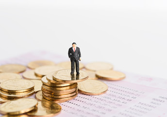 Miniature successful businessman people stand on top of golden coins with book bank background