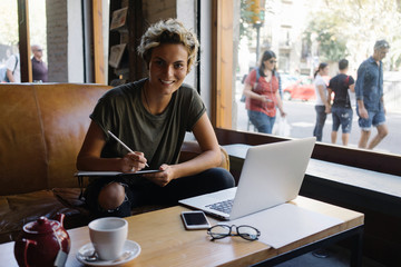 Cute tomboy girl is smiling at the camera while sitting in a modern coffee shop at the wooden table with a portable computer and a smartphone on it. Freelancer is working in a modern coworking space.