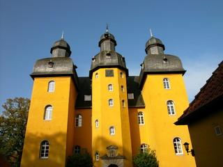 Foto auf Leinwand Schloss Goldgelb strahlende Fassade von Schloss Holte in Schloß Holte-Stukenbrock in Ostwestfalen-Lippe im Kreis Gütersloh