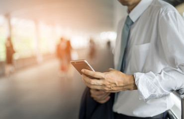 businessman holding and touch mobile phone going to working on blurred background. business concept.