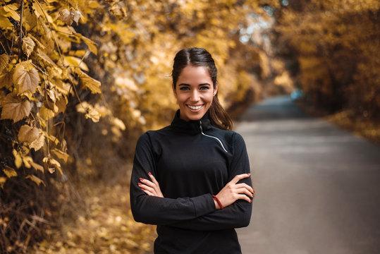 Portrait of female athlete in autumn park.