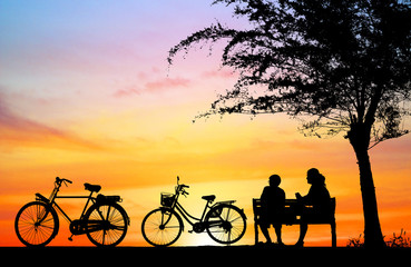 silhouette vintage bike and love couple in  the holiday on sunrise time