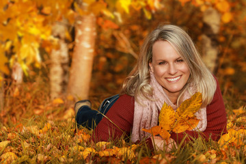 Happy middle age woman lying in autumn leaves