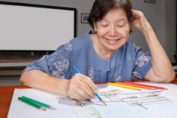 Elderly woman painting color on her drawing  , hobby at home