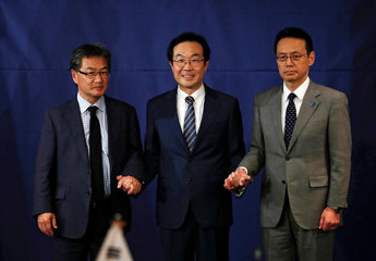 South Korean, Japanese and U.S. nuclear envoys pose for photographs during a trilateral meeting in Seoul