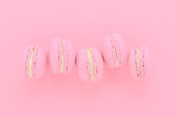 five pink macaroons homemade, on pink background, top view