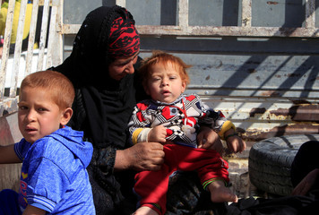 Displaced woman rides in a truck with her children as they head back to her home in Hawija