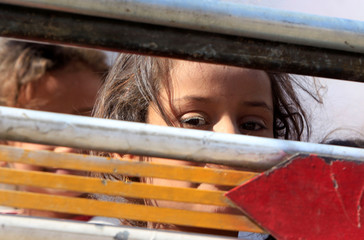 A displaced child rides in a truck with her family as they head back to her home in Hawija