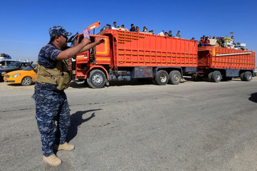 A member of Iraqi security forces stands guard as displaced people riding in trucks and cars head back to their homes in Hawija, on the outskirts of Kirkuk