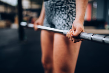 Close-Up of girl doing workout with barbell in Gym