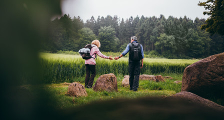 Mature Couple hiking trough green fields