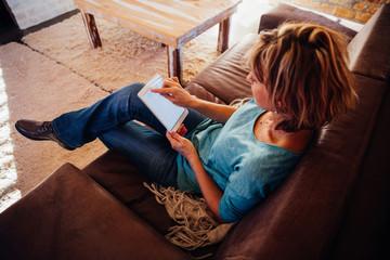 Blonde caucasian mature woman sitting on sofa using digital tablet