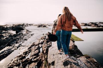 Tennager girls balancing on rocks on the beach