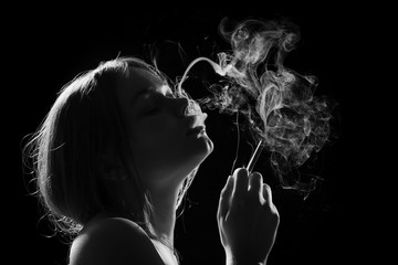 young woman smoking cigarette on black background, monochrome