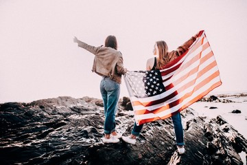 Teenager girls cheering with American flag on beach