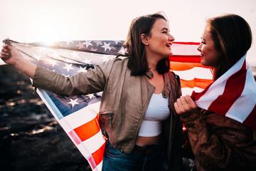 Young teenager girls having fun with USA flag Fotoväggar