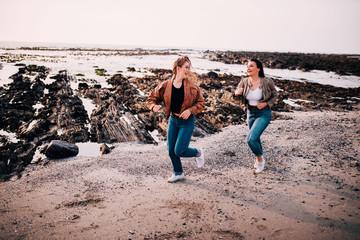 Teenager girls having fun running on the beach