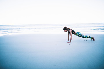 Young female athlete doing exercise on beach