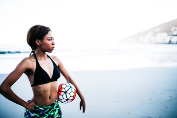 African female athlete holding soccer ball in hands