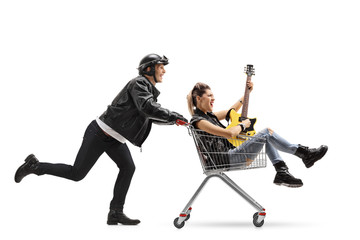 Biker pushing a shopping cart with a punk girl riding inside