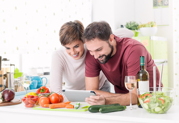 Couple cooking together and using a tablet