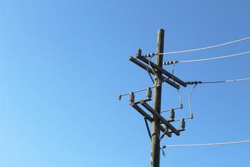 Terminal end of power pole against a deep blue sky