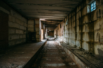 Dark tunnel in old abandoned brick factory. Abandoned industrial corridor