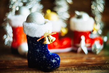 Christmas decoration.Red Santa's boot,fir tree,garland,gift,pine cones and Christmas balls.Christmas background.Soft selective focus.Winter holidays,Merry Christmas or Happy New Year concept.