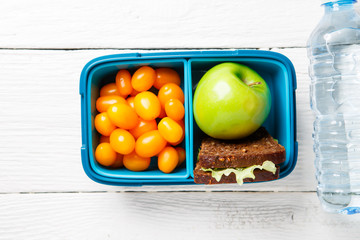 Image of cherry tomato, apple, sandwich in a container
