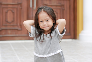 Adorable little girl smile and posing hands on head. Portrait outdoor.
