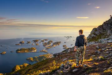 Wall Mural - Hiker standing at the top of mount Festvagtinden on Lofoten islands in Norway