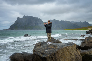 Young boy takes pictures on a mobile phone at a beach in northern Norway