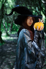 Image of young witch with pumpkin