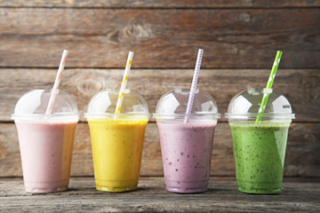 Wall Mural - Sweet smoothie in plastic cups on grey wooden table