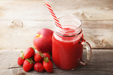 Red smoothie in glass jar with fruits on grey wooden table