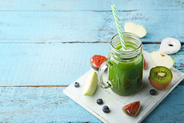 Green smoothie in glass jar with fruits on blue wooden table