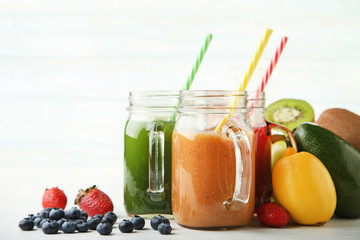 Sweet smoothie in glass jars with fruits on white background